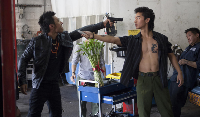 Kev Jumba wields a box cutter. Man behind him is not impressed.